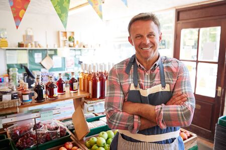 Portrait Of Mature Man Running Organic Farm Shop Foto de archivo