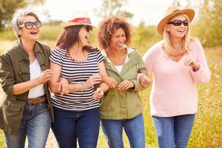 Grupo de amigas maduras caminando por el sendero a través del camping de yurtas