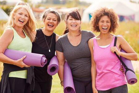 Portret van volwassen vrouwelijke vrienden op yoga-retraite in de buitenlucht die langs het pad door de camping lopen Stockfoto