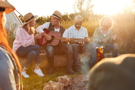 Group Of Mature Friends Sitting Around Fire As They Drink And Sing Songs At Outdoor Campsite Фото со стока