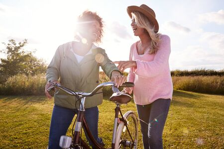 Two Mature Female Friends Walking Along Path With Bike Through Yurt Campsite