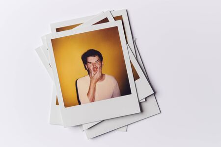 Stack Of Instant Film Photos From Modeling Casting In Studio With Shot Of Young Man On Top