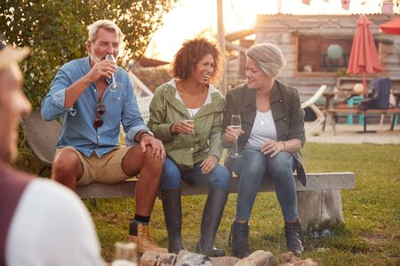 Group Of Mature Friends Sitting Around Fire And Drinking At Outdoor Campsite Bar Фото со стока - 134160546