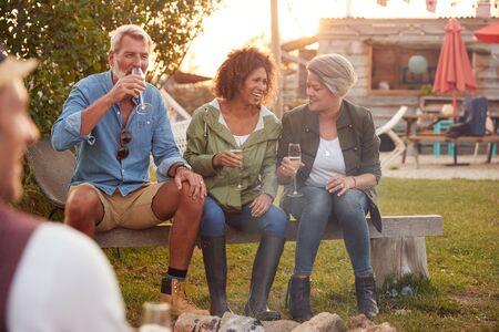 Gruppe älterer Freunde, die am Feuer sitzen und in der Outdoor-Campingbar trinken? Standard-Bild