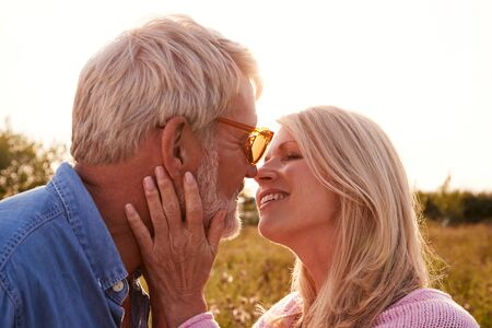 Loving Mature Couple In Countryside About To Kiss Against Flaring Sun Фото со стока - 134160547