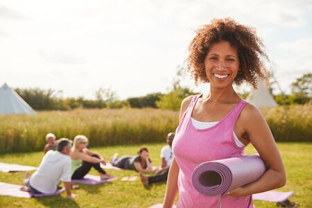 Portrait Of Mature Woman On Outdoor Yoga Retreat With Friends And Campsite In Background Stockfoto