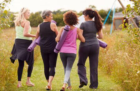 Rückansicht von reifen Freundinnen auf Outdoor-Yoga-Retreat zu Fuß entlang des Weges durch den Campingplatz