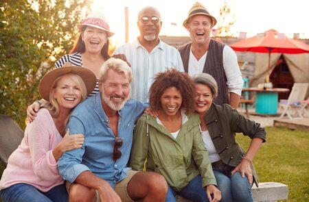 Portrait Of Mature Friends Sitting Around Fire At Outdoor Campsite