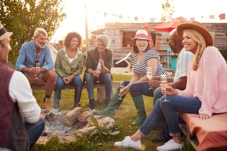 Group Of Mature Friends Sitting Around Fire And Drinking At Outdoor Campsite Bar Archivio Fotografico