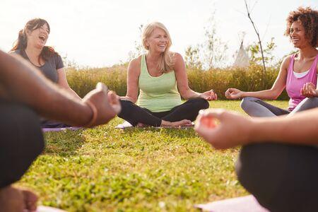 Gruppe von reifen Männern und Frauen in der Klasse im Outdoor-Yoga-Retreat sitzender Kreis meditieren