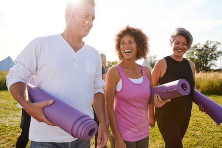 Group Of Mature Men And Women With Exercise Mats At End Of Outdoor Yoga Class