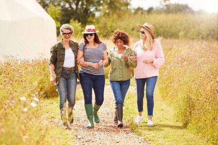 Gruppo di amiche mature che camminano lungo il percorso attraverso il campeggio Yurt
