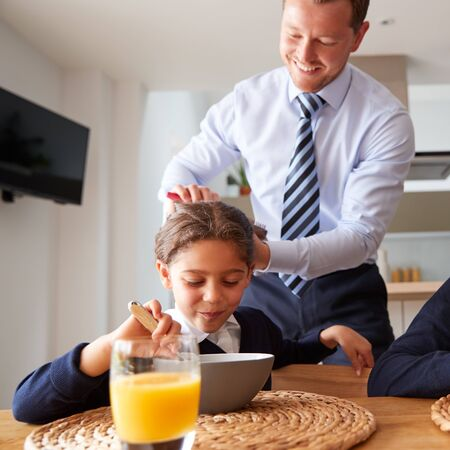 Businessman Father In Kitchen Brushing Hair And Helping Children With Breakfast Before School Banco de Imagens