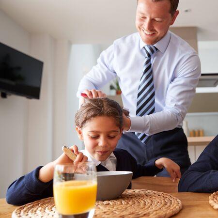 Padre empresario en la cocina cepillarse el cabello y ayudar a los niños con el desayuno antes de la escuela
