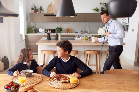 Children Wearing School Uniform Eating Breakfast As Father Gets Ready For Work