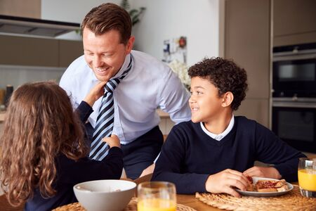 Daughter Helping Businessman Father To Put On Tie As Children Eat Breakfast In Kitchen Before School