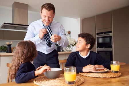 Children Eating Breakfast Before School As Father Get Ready For Work In Office