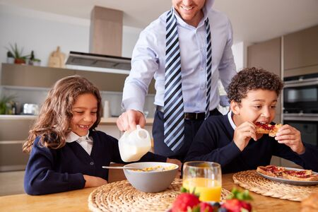 Businessman Father In Kitchen Helping Children With Breakfast Before Going To School Banco de Imagens