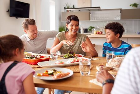 Multi-Generation Mixed Race Family Eating Meal Around Table At Home Together Фото со стока