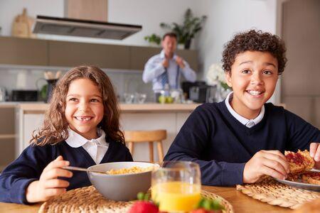 Portrait Of Children Wearing School Uniform Eating Breakfast As Father Gets Ready For Work