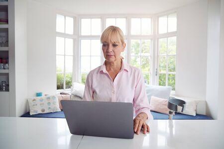 Femme handicapée d'âge mûr avec des béquilles à la maison Working On Laptop On Kitchen Counter Banque d'images