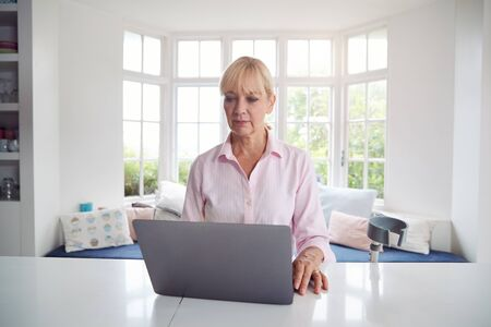 Mature Disabled Woman With Crutches At Home Working On Laptop On Kitchen Counter Stock Photo