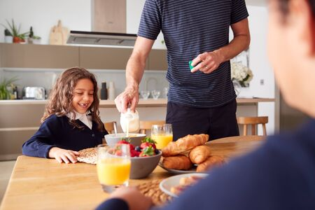 Father In Kitchen Helping Children With Breakfast Before Going To School Banco de Imagens