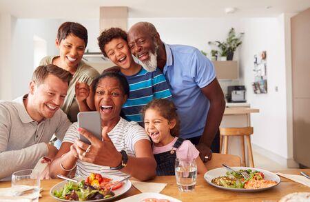 Famille de race mixte multigénérationnelle posant pour un selfie alors qu'ils mangent un repas autour d'une table à la maison ensemble