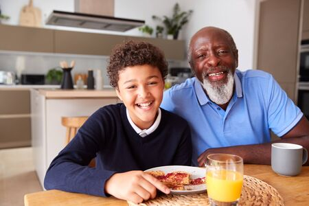 Portrait Of Smiling Grandfather Sitting In Kitchen With Grandson Eating Breakfast Before School Banco de Imagens