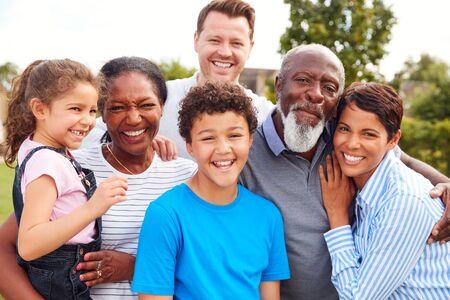 Retrato de familia de raza mixta multigeneracional sonriente en el jardín de casa