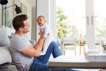 Baby Daughter Sitting On Fathers Lap As He Plays Game With Her At Home Stock Photo
