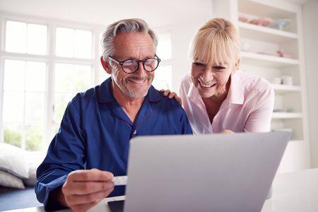 Älteres Paar zu Hause nach Informationen über Medikamente online mit Laptop suchen Standard-Bild