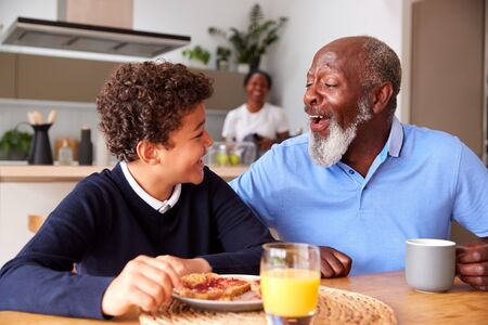 Grandparents Sitting In Kitchen With Grandson Eating Breakfast Before Going To School
