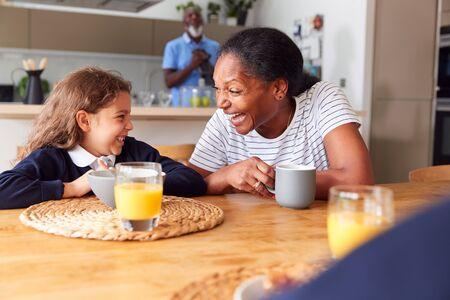 Grandparents Sitting In Kitchen With Grandchildren Eating Breakfast Before Going To School Banco de Imagens