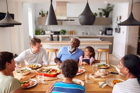 Multi-Generation Mixed Race Family Eating Meal Around Table At Home Together Stock Photo