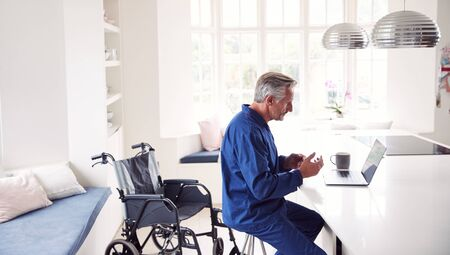 Mature Disabled Man In Wheelchair At Home Using Laptop On Kitchen Counter