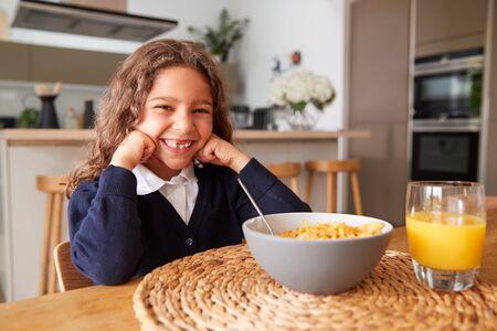 Portrait Of Girl Wearing Uniform In Kitchen Eating Breakfast Cereal Before Going To School