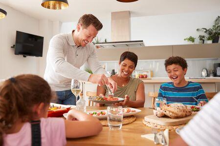 Père servant de famille métisse multigénérationnelle manger un repas autour d'une table à la maison ensemble