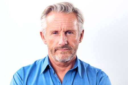 Studioaufnahme eines reifen Mannes mit ernstem Ausdruck vor weißem Hintergrund in die Kamera