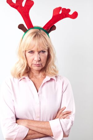 Studio Shot Of Unhappy Mature Woman Wearing Dressing Up Reindeer Antlers Against White Background Фото со стока