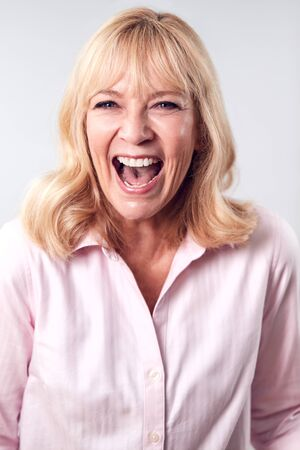 Studio Shot Of Laughing Mature Woman Against White Background At Camera