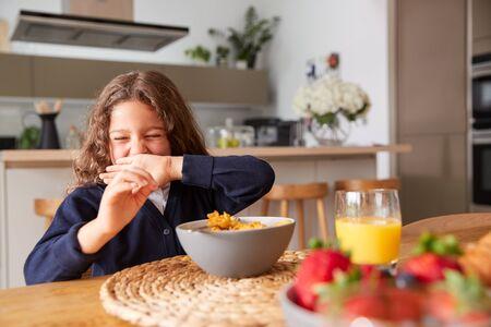 Girl Wearing Uniform In Kitchen Eating Breakfast Cereal Before Going To School