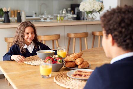 Children Wearing Uniform In Kitchen Eating Breakfast Before Going To School Banco de Imagens