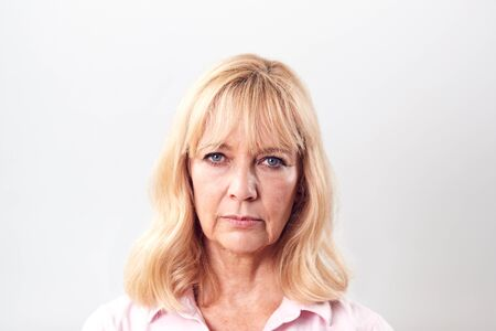 Studio Shot Of Unhappy And Frustrated Mature Woman Against White Background At Camera Banco de Imagens
