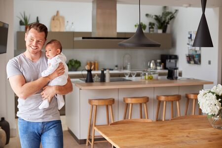 Portrait Of 3 Month Old Baby Daughter Being Held By Loving Father In Kitchen At Home 写真素材