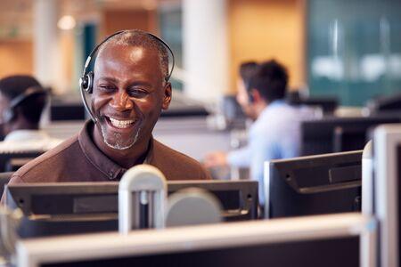 Uomo d'affari maturo che indossa le cuffie del telefono che parla con il chiamante nel dipartimento dei servizi ai clienti