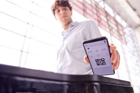 Male Passenger In Airport Departure Lounge Scanning Digital Boarding Pass On Smart Phone Imagens