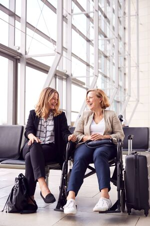 Businesswoman Sitting In Airport Departure With Female Colleague In Wheelchair Talking Together