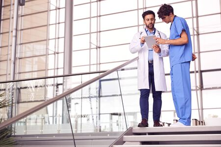 Two Male Doctors Having Informal Meeting In Modern Hospital Looking At Digital Tablet