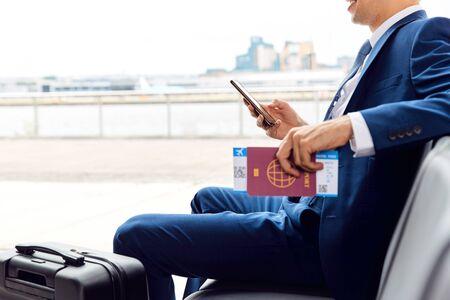 Geschäftsmann mit Reisepass und Bordkarte sitzen in der Abflughalle des Flughafens mit Handy